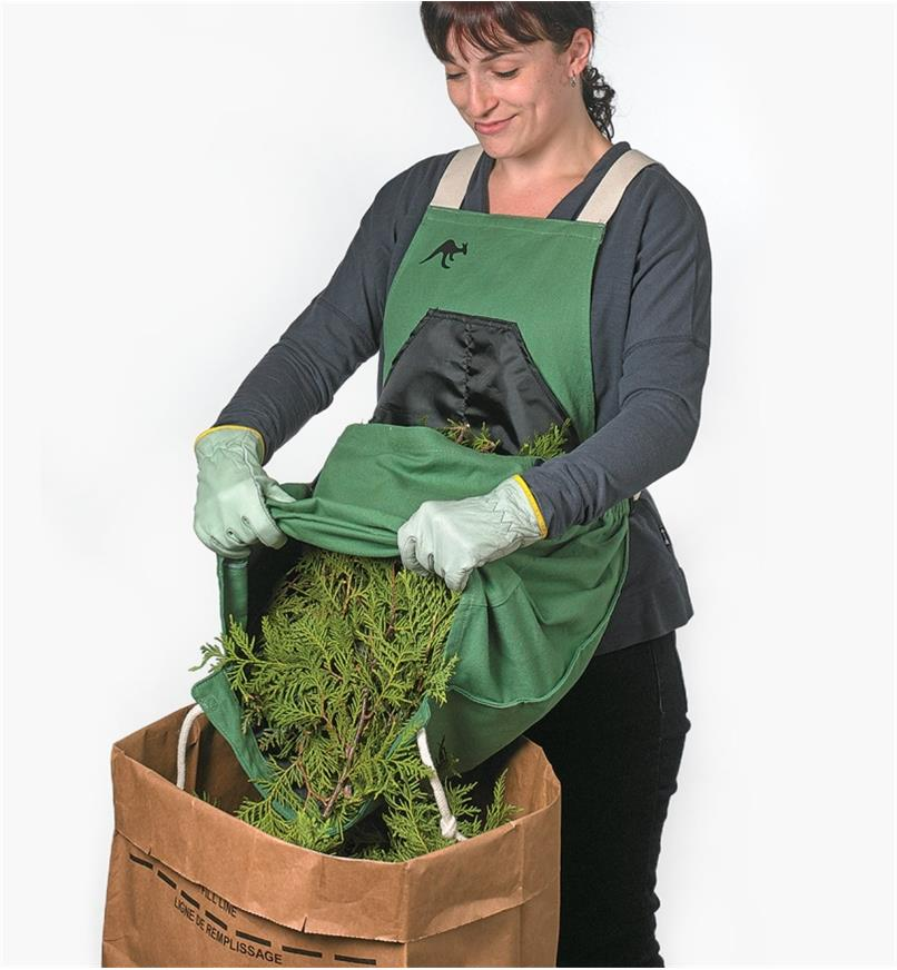 A woman wearing the kangaroo pocket apron dumps cedar trimmings from the pocket into a paper bag