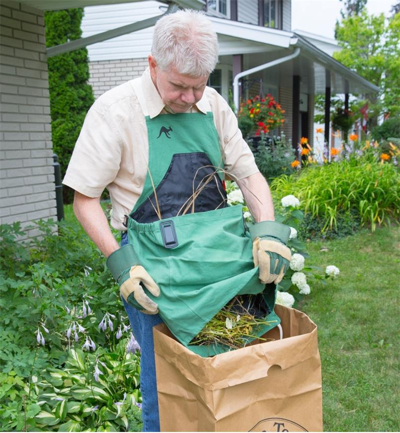 A woman wearing the kangaroo pocket apron dumps garden waste from the pocket into a paper bag