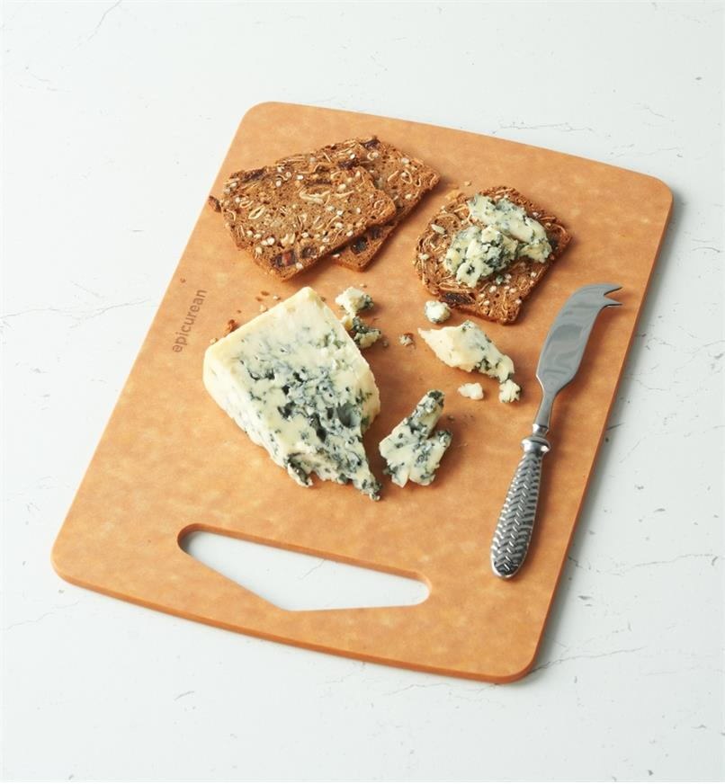 A knife, cheese and crackers on a Small Epicurean Prep Series Cutting Board