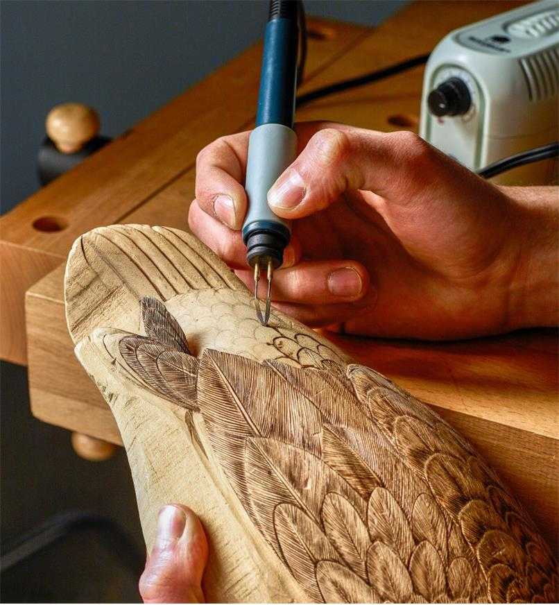Burning feather designs onto a wooden duck