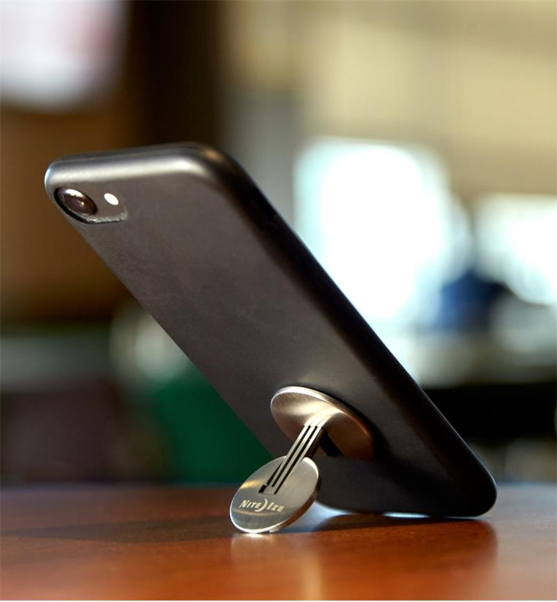 Nite Ize FlipOut Handle & Stand attached to a phone, folded out to prop the phone on a tabletop