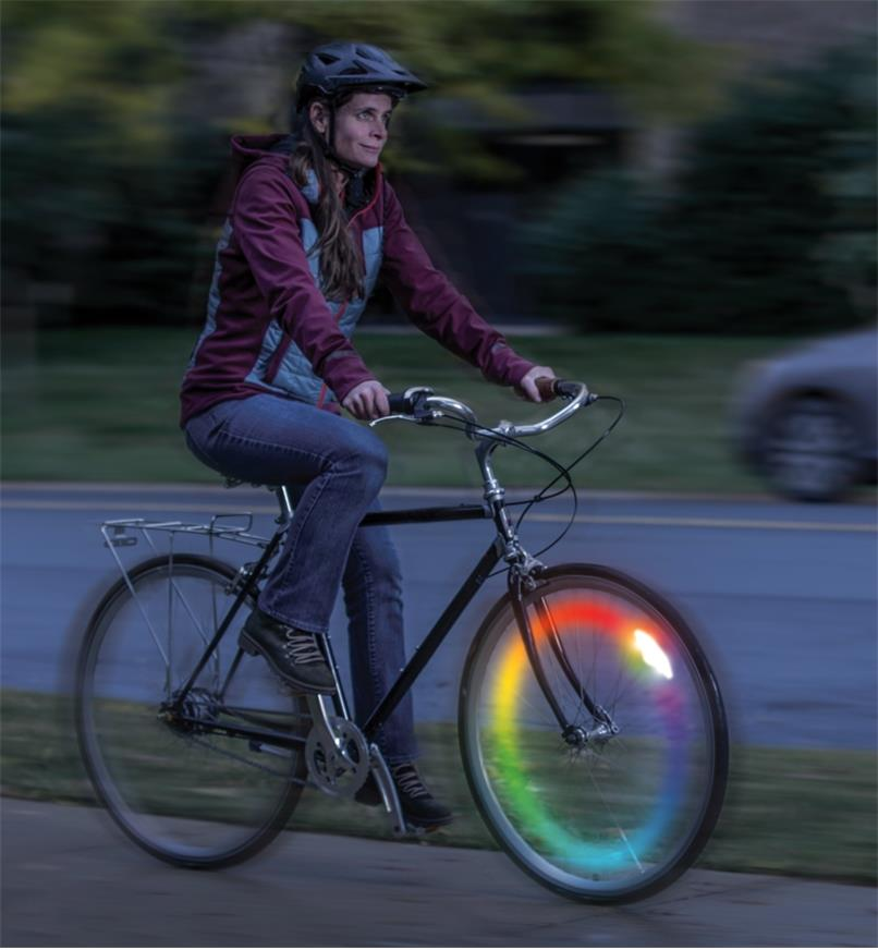 A woman rides a bicycle at night with a SpokeLit wheel light installed in color-changing mode