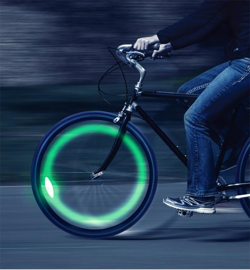 Riding a bicycle at night with a SpokeLit wheel light installed glowing green