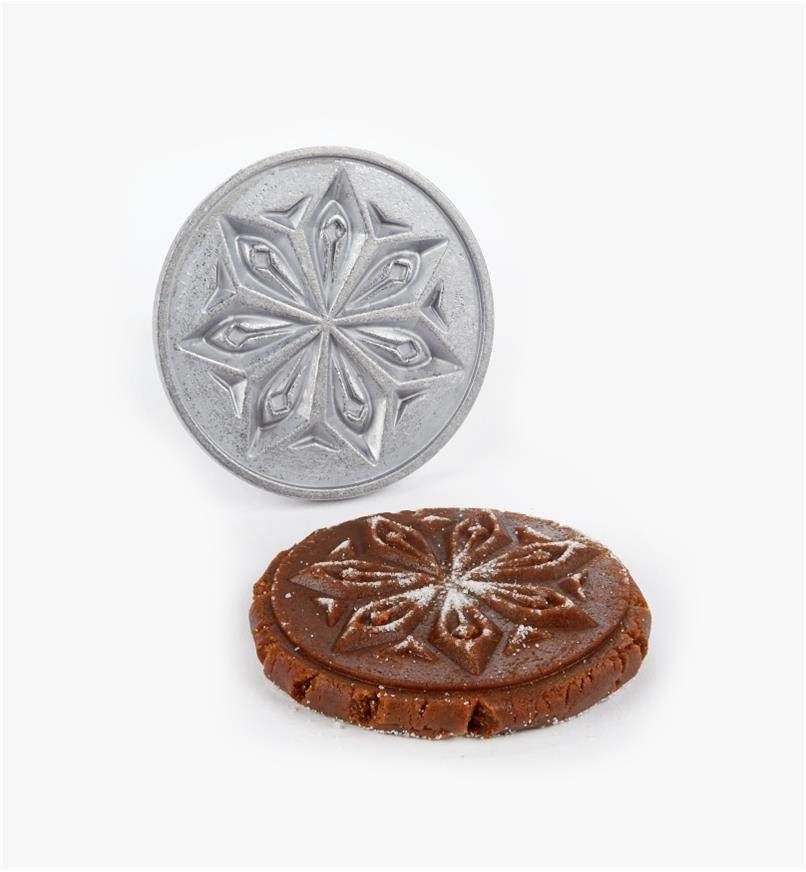 Snowflake stamp next to a cookie with the design stamped on it