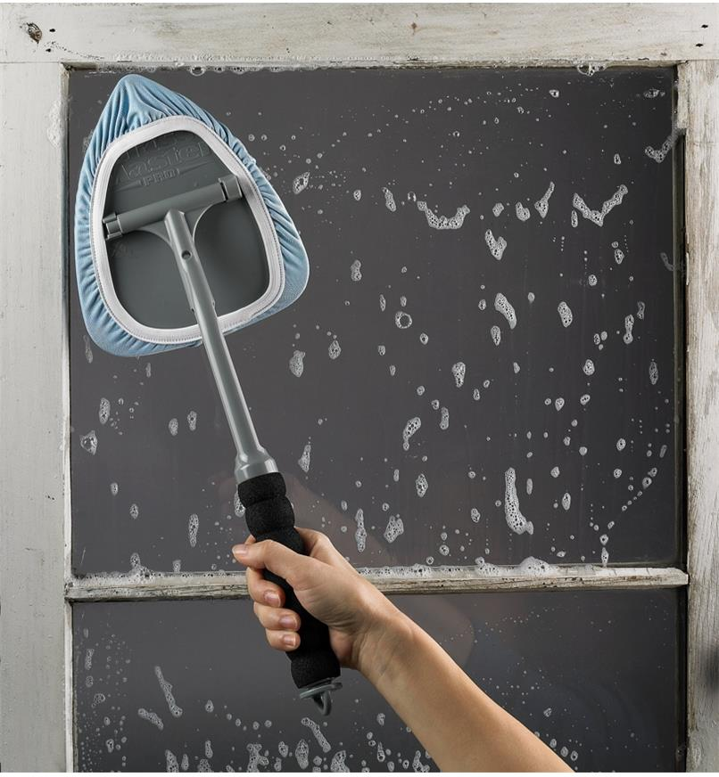 Using the Glass and Surface Cleaner to wash a window