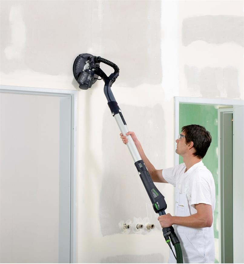 A man sanding drywall above a door with a Planex LHS-E 225 Easy Drywall Sander