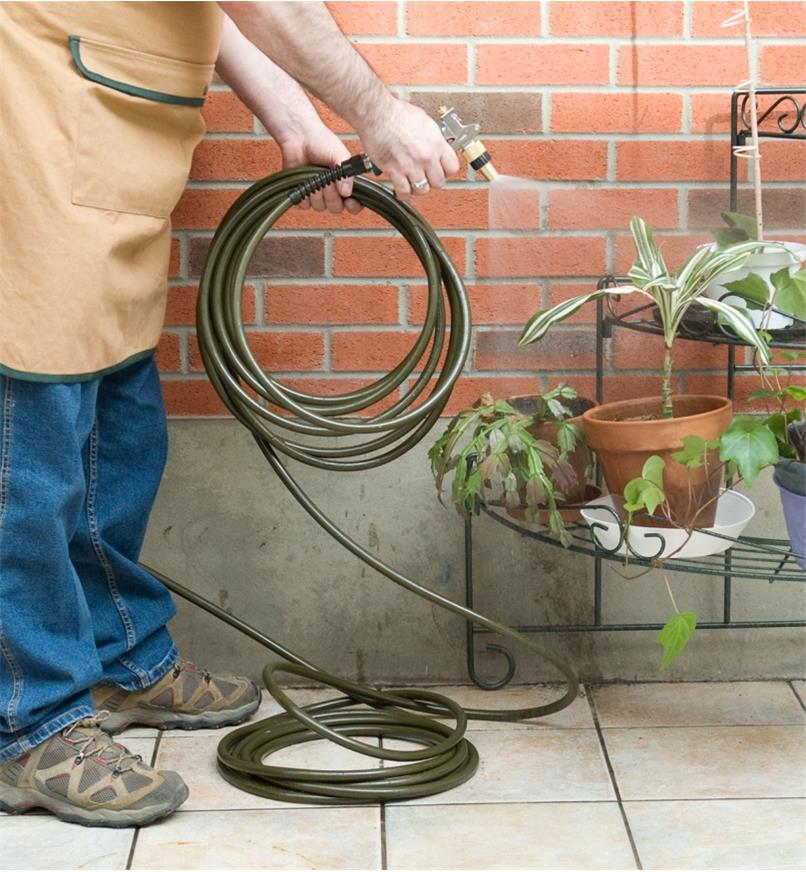 A man uses the lightweight hose to spray potted plants