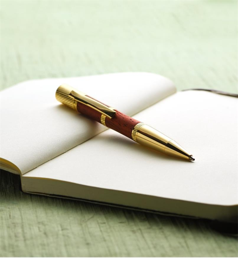 Example of a Pensar gold pen turned from a wood blank, lying on an open notebook