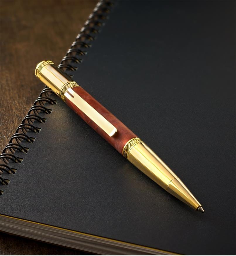 Stylo Sierra Diverse doré déposé sur un cahier à spirale noir