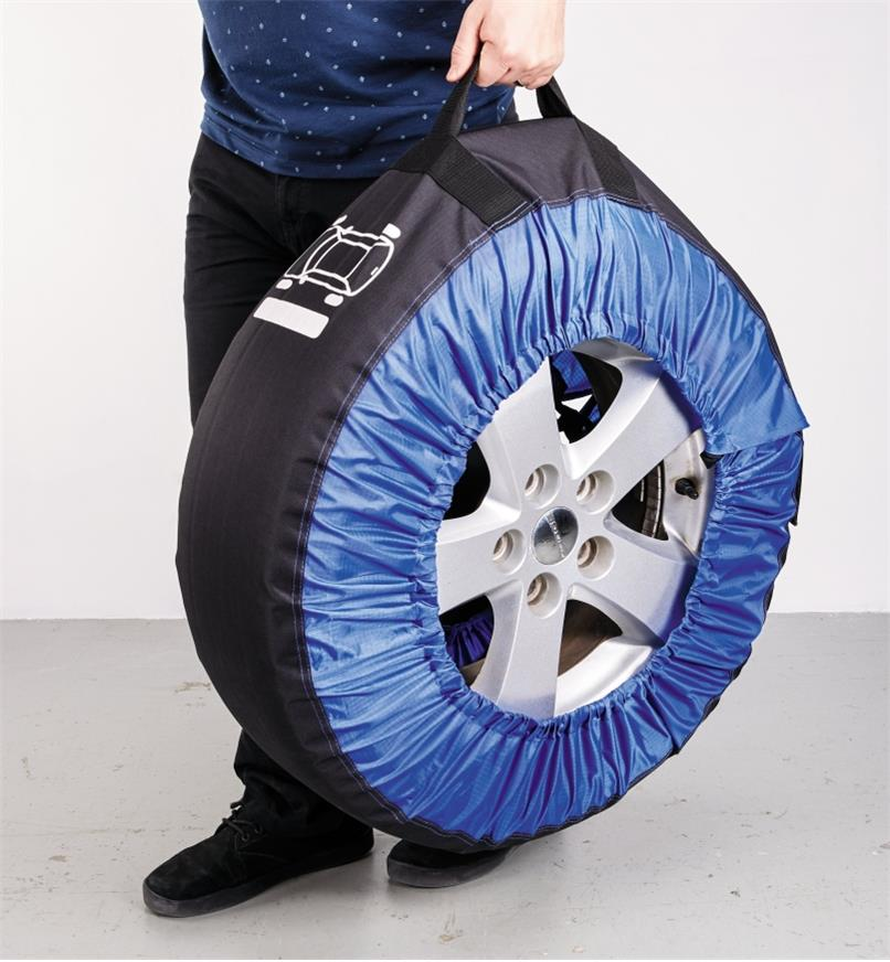 A man carries a tire in a tire bag