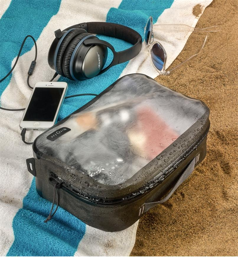 A closed RunOff medium packing cube filled with items lies on a beach towel with a cell phone, headphones and sunglasses nearby