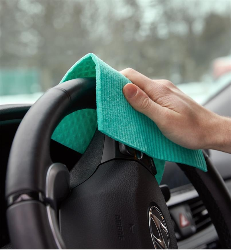 Wiping a car steering wheel using a reusable household paper towel