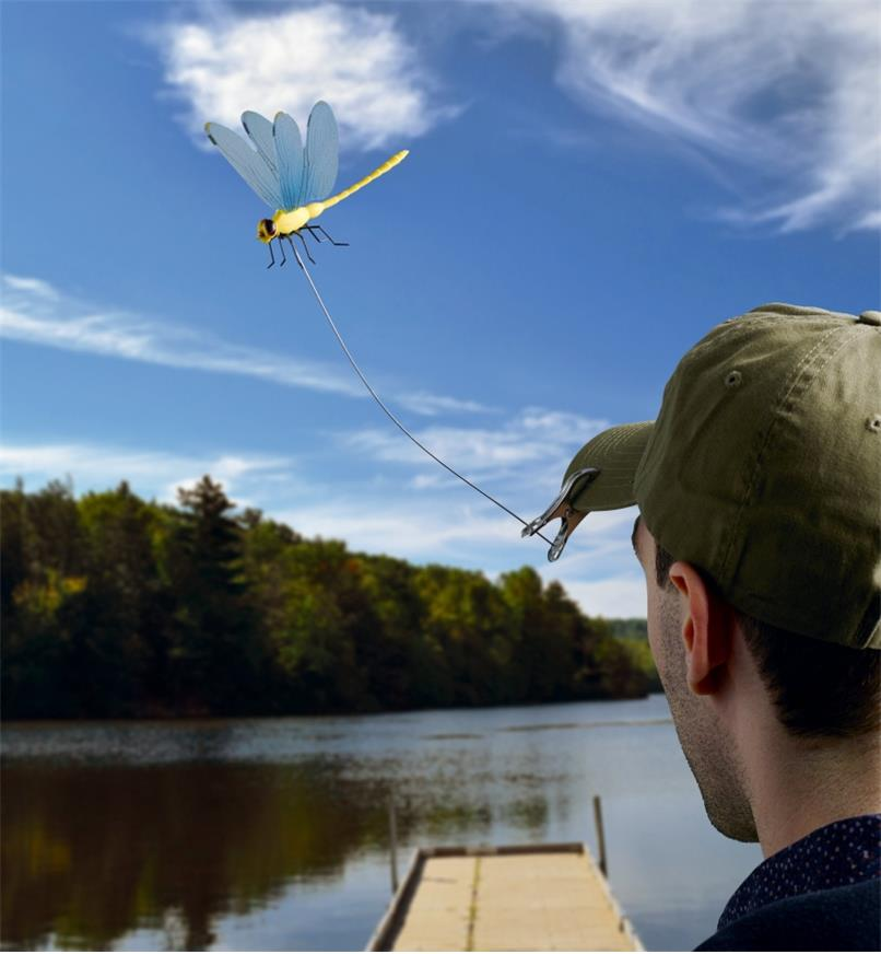 A man wears a ball cap with a Dragonfly Wingman deer fly and horsefly deterrent clipped to the peak