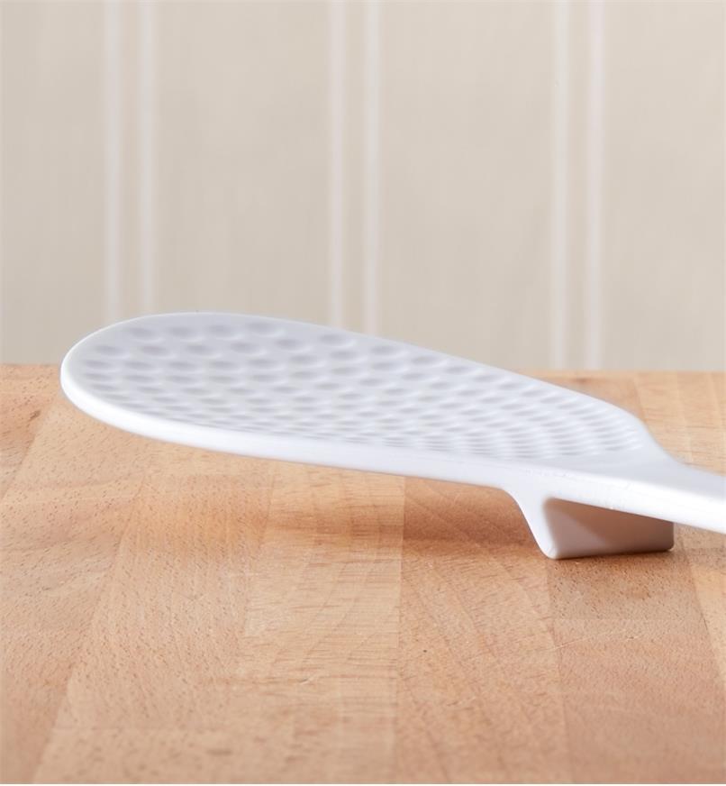 Cuillère à riz avec son petit pied au dos pour dégager le cuilleron sur un comptoir en bois