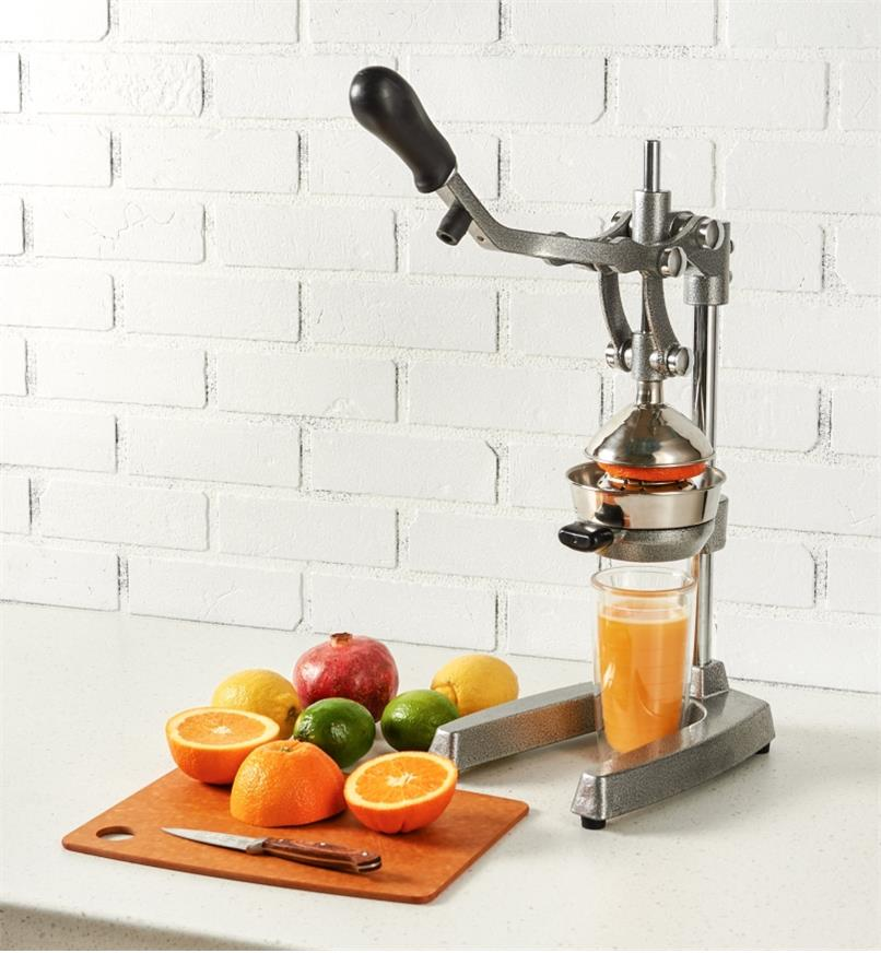 Juice Press on a counter being used to squeeze a glass of orange juice