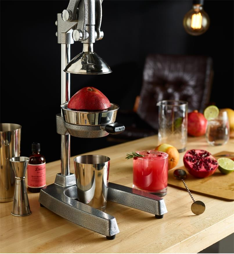 A juice press in a home bar setting, used to squeeze a fresh pomegranate