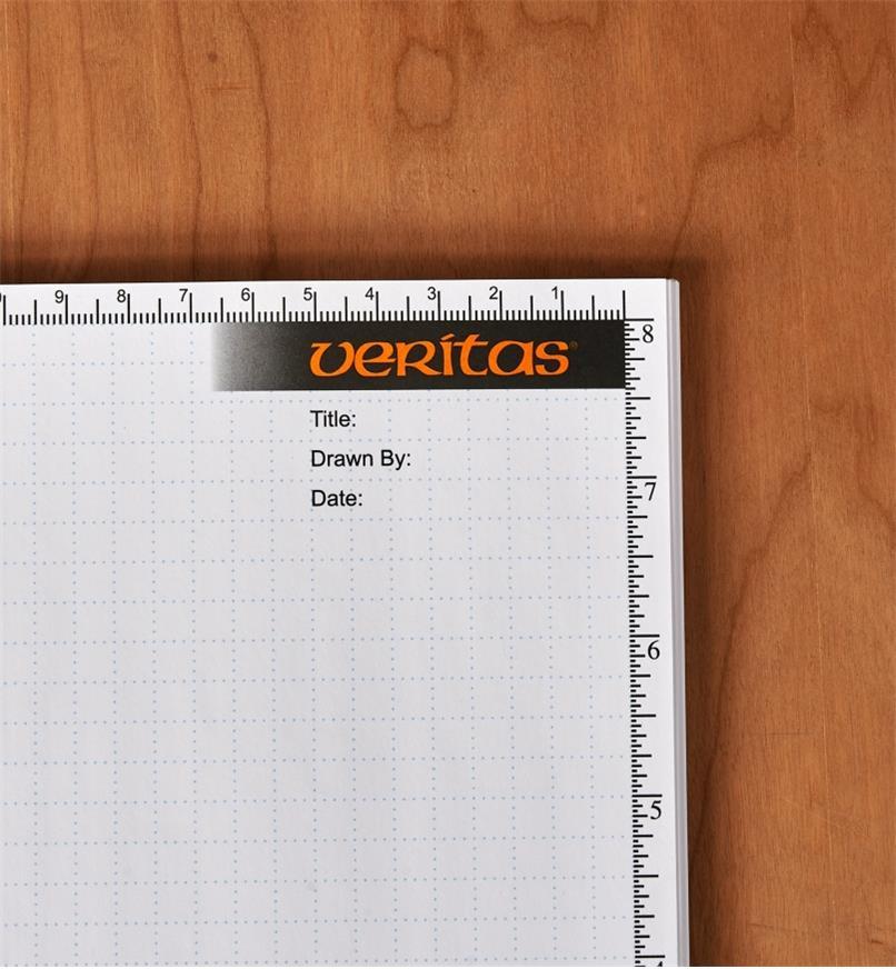 Partie supérieure droite d'une page de cahier quadrillé à spirale montrant le logo Veritas, des espaces pour indiquer le titre, le nom du dessinateur et la date, des graduations métriques par intervalles de 1 mm sur le bord supérieur et des graduations impériales par intervalles de 1/32 po sur le bord droit