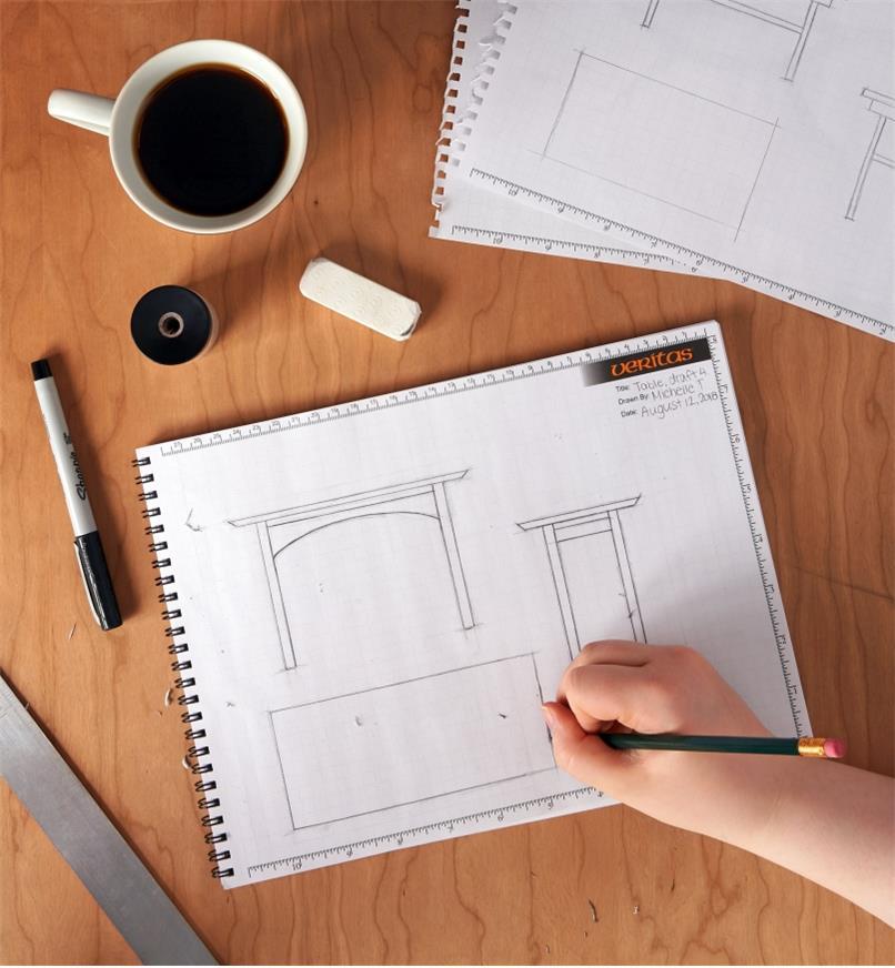 Personne réalisant des dessins au crayon dans un cahier quadrillé à spirale ouvert près d'une règle, d'un marqueur permanent, d'un aiguisoir, d'une tasse de café, d'une efface et de deux feuilles détachées