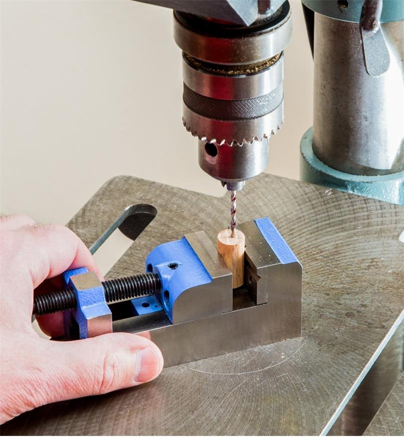 A drill press is used to drill a hole in a small piece of wood that is held in the toolmaker's vise.