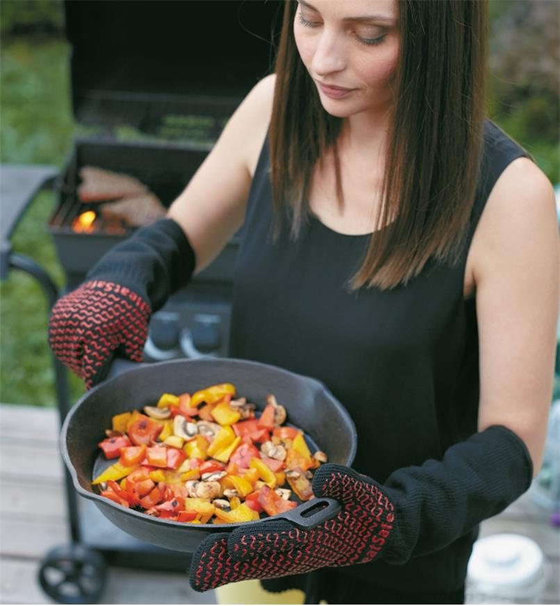 Person wearing barbecue gloves holding cast-iron pan they have removed from barbecue.