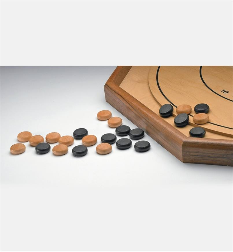 Crokinole/Checker Pieces piled next to a crokinole board