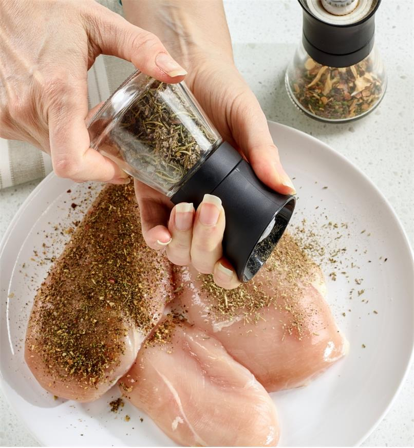 CrushGrind mill grinding a herb blend onto chicken