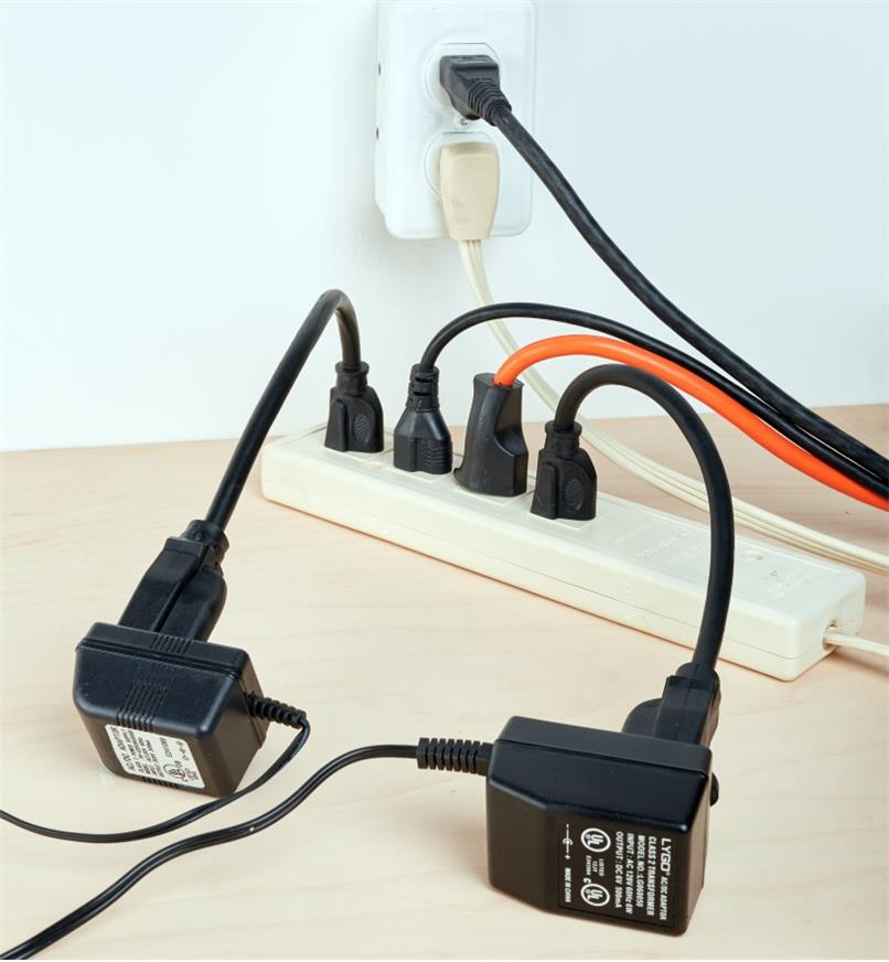 """Two chargers plugged into a power bar using 12"""" outlet extenders"""