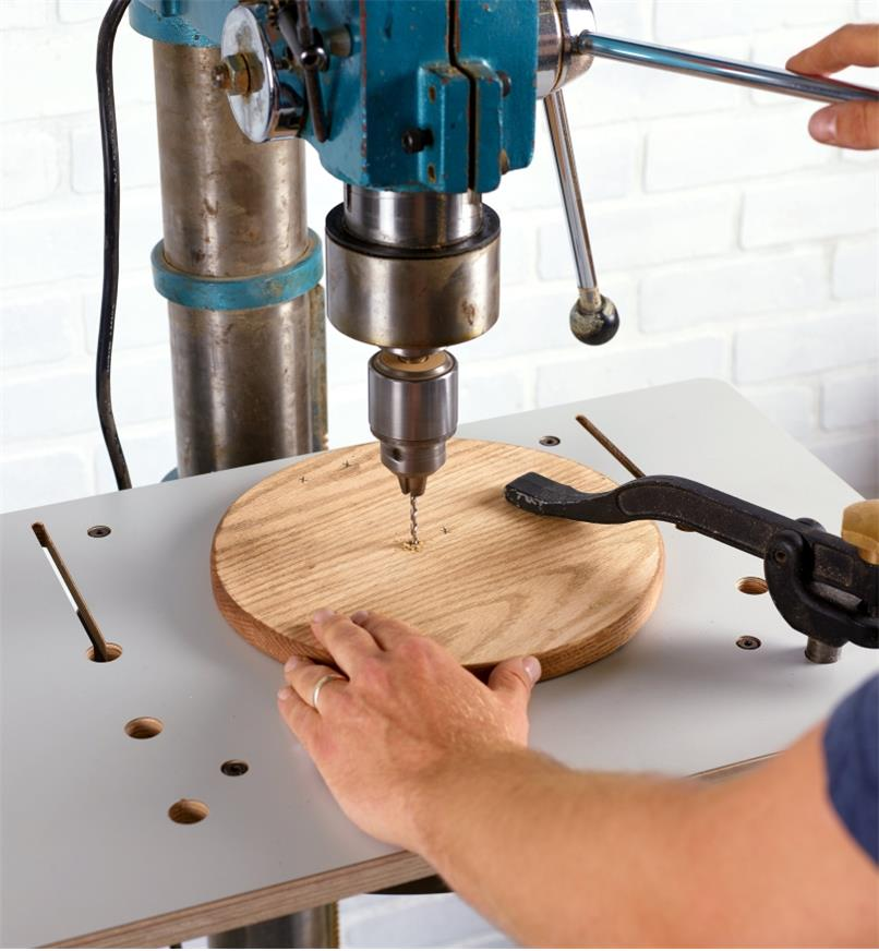 """A workpiece secured with a hold-down clamp set in one of the 3/4"""" dog holes in the drill-press table"""