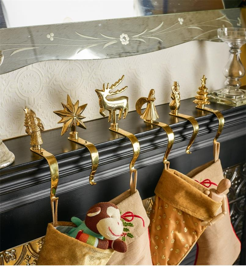 Set of 6 Brass Hangers holding stockings on a mantel