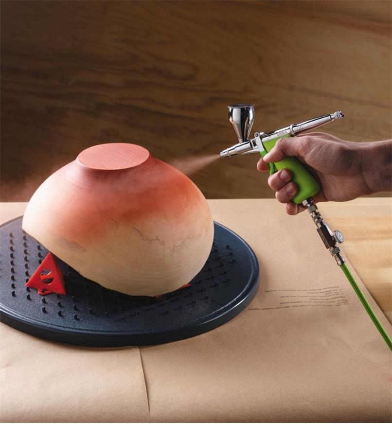 Spraying paint on the bottom of a bowl with the Grex Airbrush Kit with Top-Mount Cup