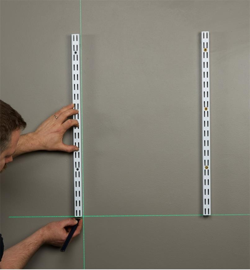 A green crosshair laser level beam is projected onto a wall, allowing an installer to ensure shelf tracking is level and plumb