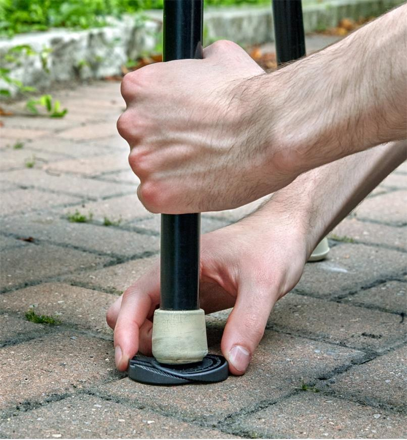 Wedging the adjustable furniture leveller under the leg of a patio chair