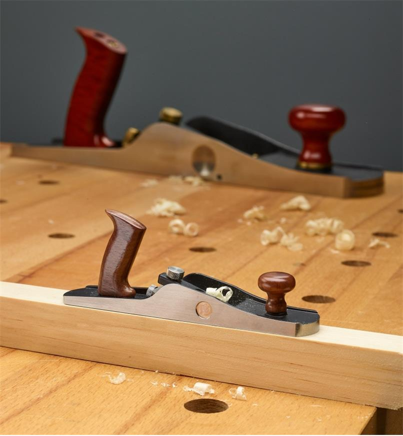 The miniature bevel-up jack plane sits on a workpiece with a full-size low-angle jack plane shown in the background