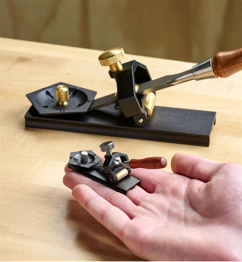 The miniature honing guide is held on the fingers of an open hand while the full-size honing guide appears in the background