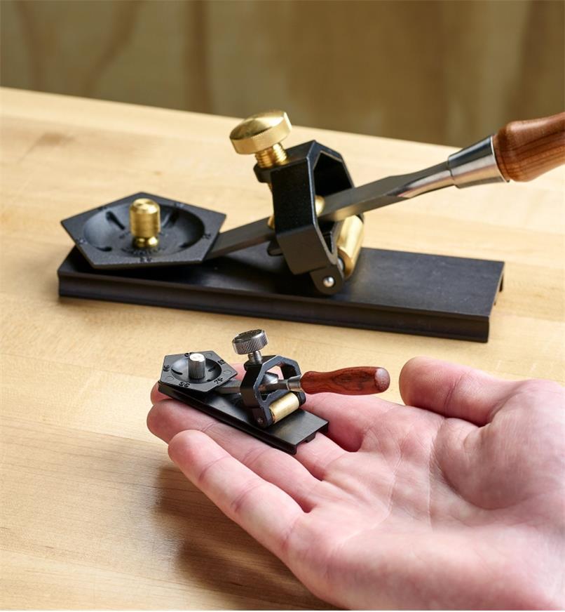 Guide d'affûtage miniature dans une main ouverte et modèle pleine grandeur de l'ensemble d'affûtage en arrière-plan