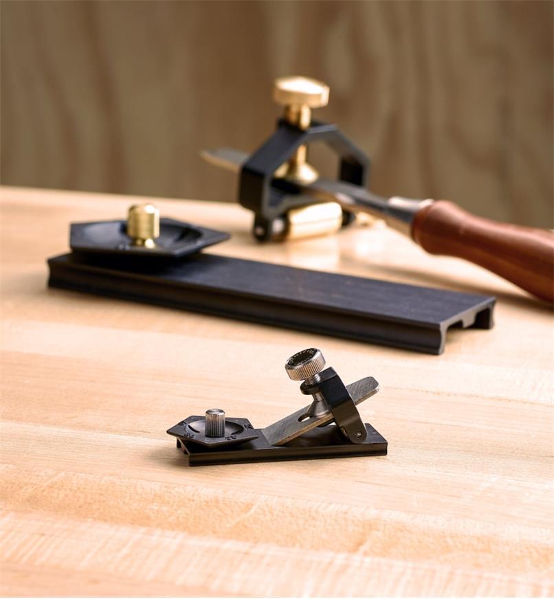 Guide d'affûtage miniature avec une petite lame posée sur le gabarit d'angle avec, en arrière-plan, un modèle pleine grandeur de l'ensemble d'affûtage