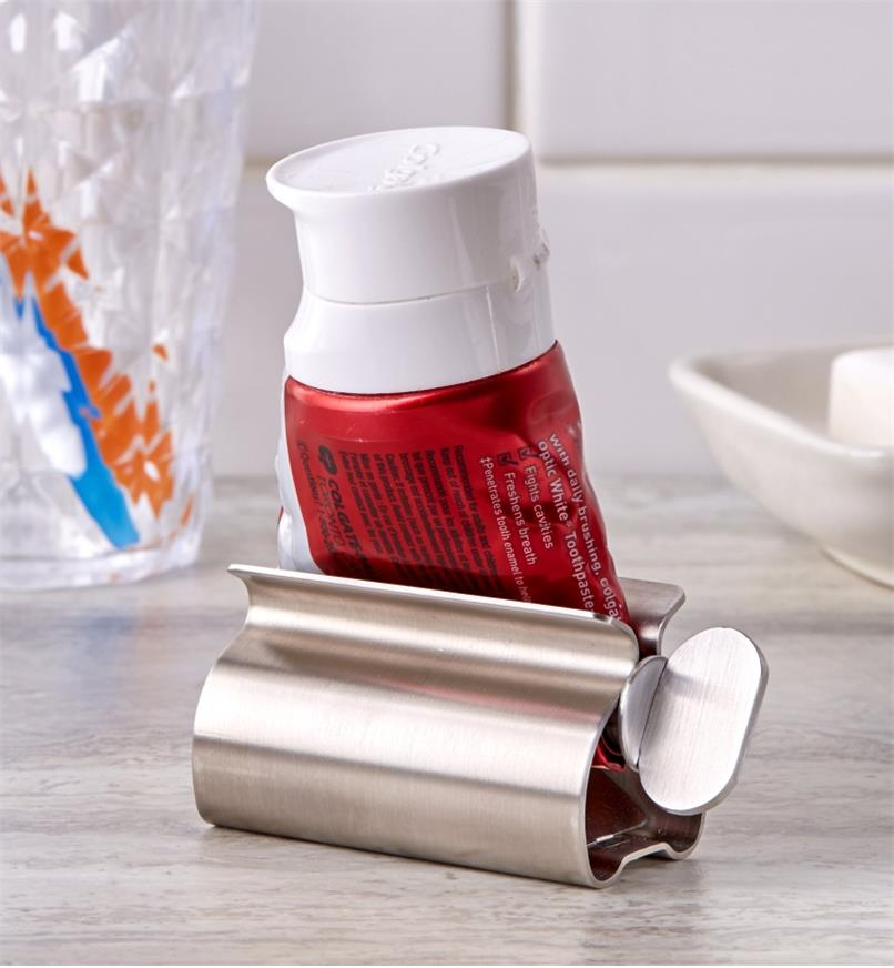 The tube squeezer holding a rolled-up tube sits on a bathroom counter