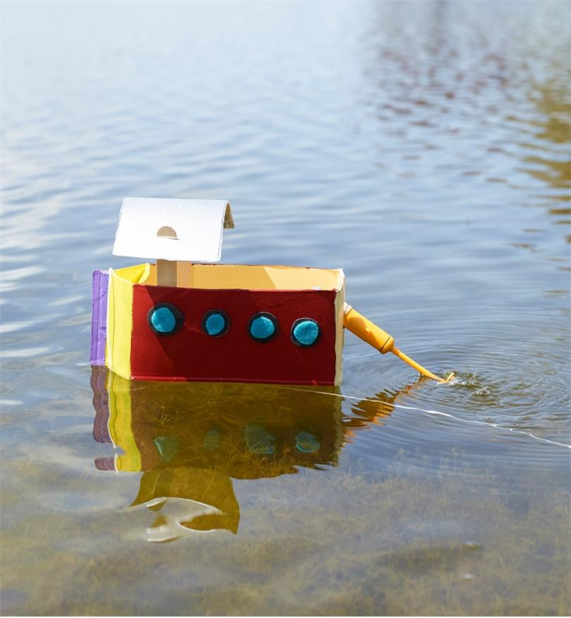 Make Your Own Motor Boat motor attached to a homemade toy boat cruising in a lake