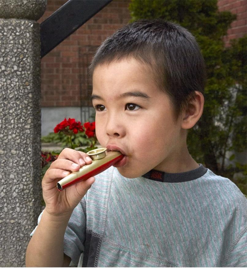 Enfant jouant du gazou métallique traditionnel