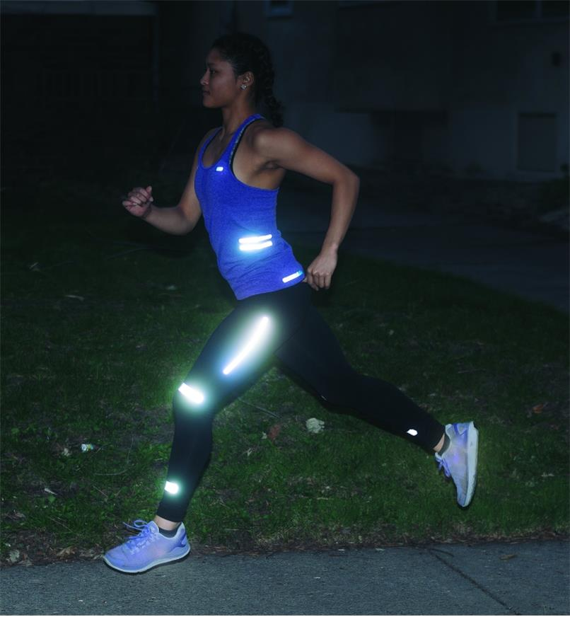 A woman running at night with Iron-On & Peel-and-Stick Reflective Strips applied to her clothing