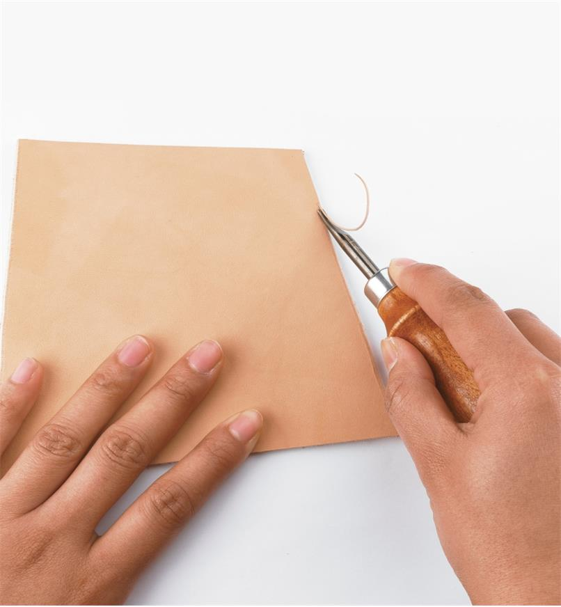 Using an edging tool to cut a radiused profile on a piece of leather