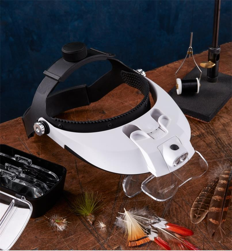 An LED headband magnifier, with two magnification lenses mounted and three stored in the case, shown on a fly-tying bench along with assorted fly-tying materials, tools and finished flies