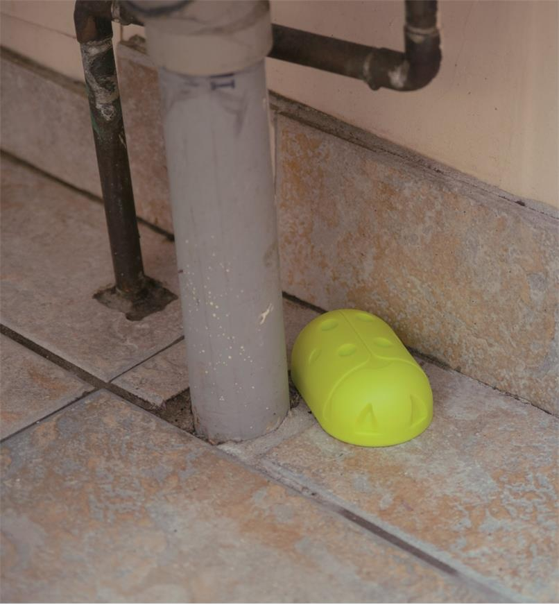 Earwig Trap placed on a floor beside a pipe