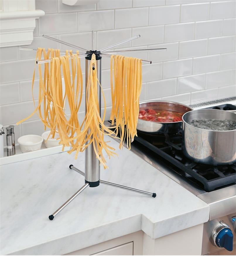 Collapsible Pasta Drying Rack on a counter, drying strands of spaghetti