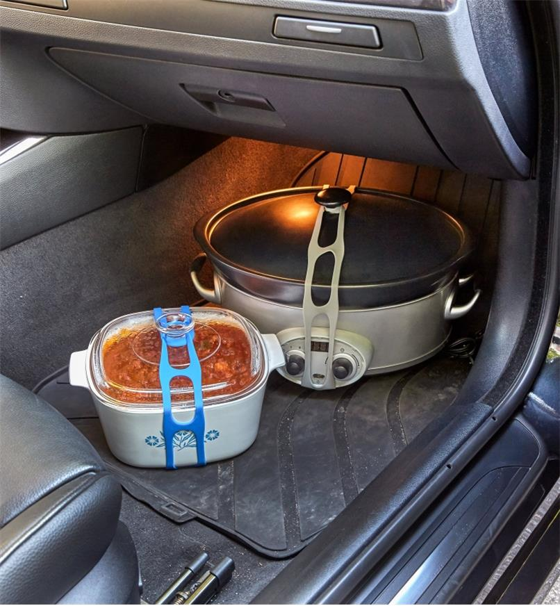 Casserole dish and slow-cooker pot held closed with lid latches in a car's passenger-side footwell