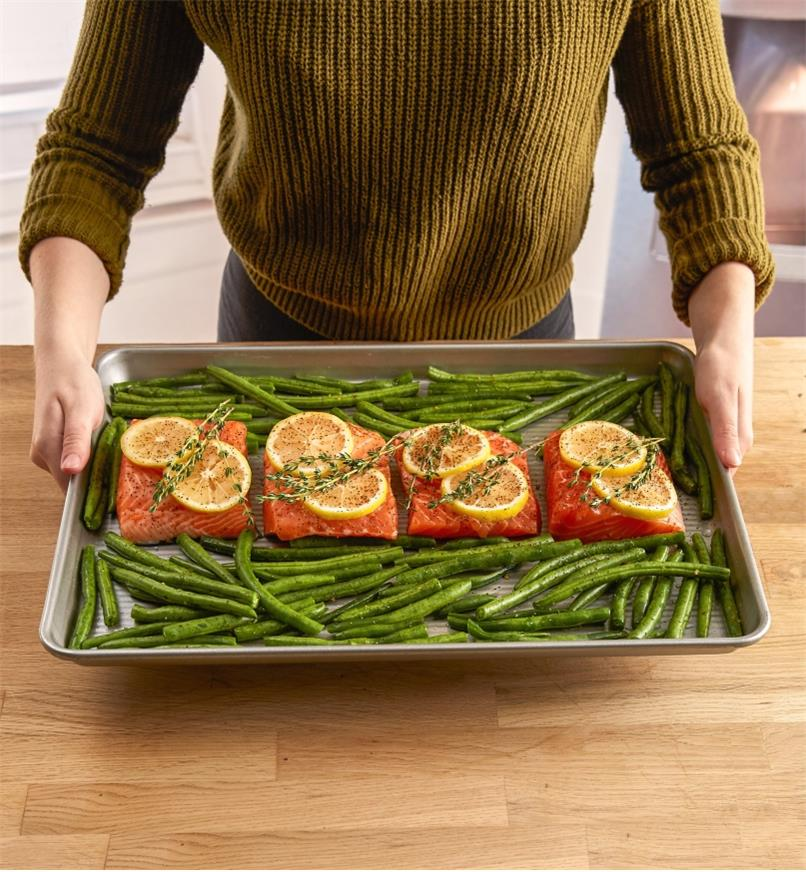 Half sheet baking pan containing salmon pieces and string beans