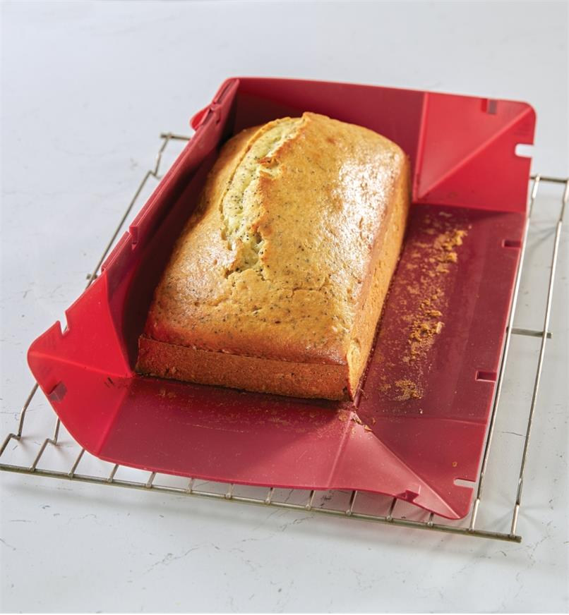 The sides of the collapsible silicone loaf pan are detached to remove a freshly baked loaf