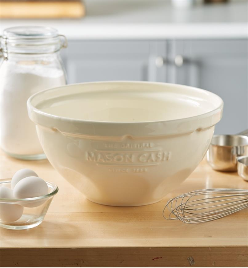 A Mason Cash mixing bowl sits on a kitchen countertop near utensils and ingredients