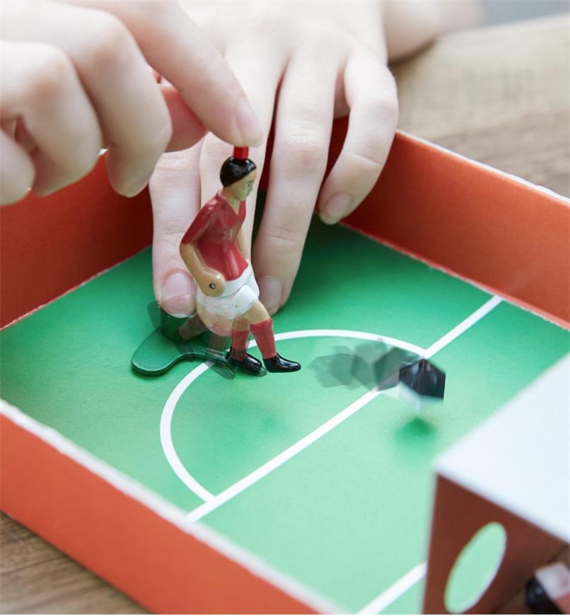 Joueur activant la jambe du tireur Tipp-Kick en appuyant sur le bouton de sa tête