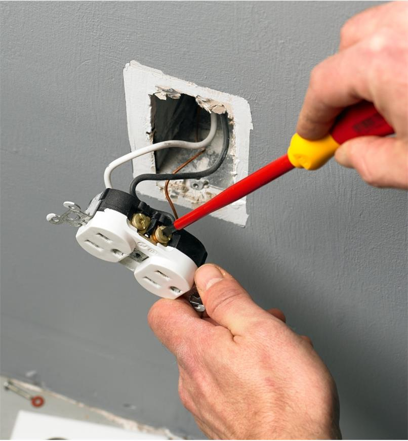 Fixing an electrical outlet with a Wiha insulated screwdriver